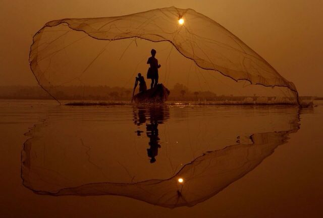 Fishermen casting his net on the placid waters of Godavari river, India. Photograph by K.R.Deepak