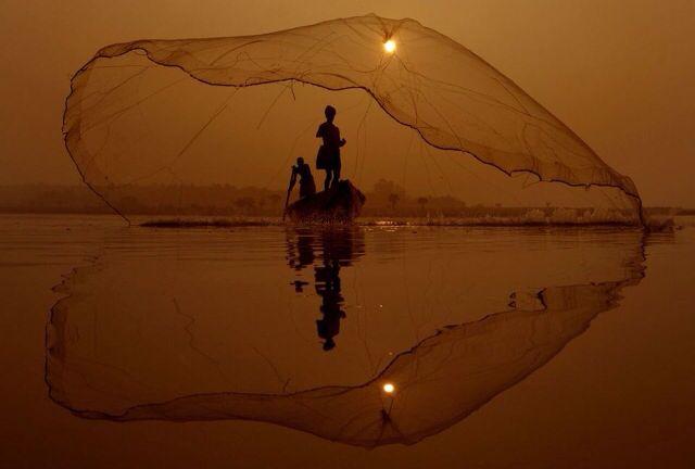 Fishermen casting his net on the placid waters of Godavari river, India. Photograph by K.R.Deepak