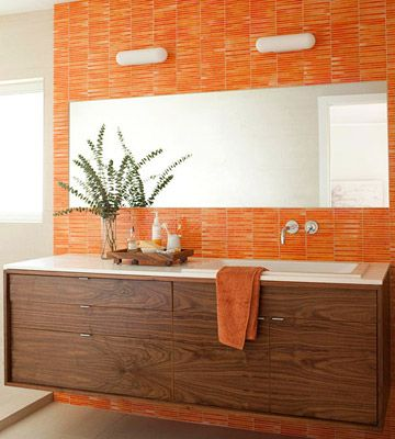Vibrant Orange: An orange tile accent wall lets the color do the talking in this vibrant bathroom. A large frameless mirror balances the bold hue and adds to the horizontal effect of the space.