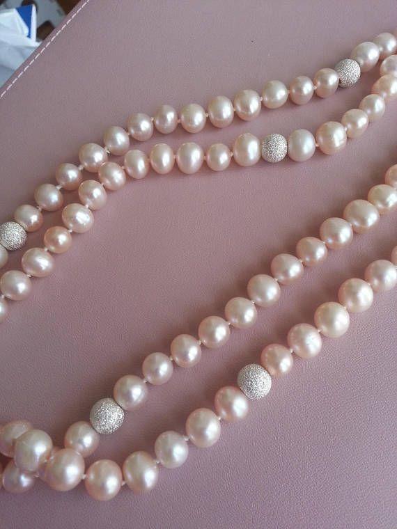 Ce collier est composé de perles de culture deau douce de couleur pêche ainsi que de boules dargent travaillé pour être brillant. - Longueur: environ 95 cm - perles de culture arrondies mais pas tout-à-fait rondes - diamètre des perles: environ 0.8 cm - diamètre des boules dargent: environ 0.7 cm La couleur des perles de ce collier est très douce et se marrie facilement avec dautres couleurs. Ce collier est un accessoire facile à porter et apporte à lui seul une touche délégance à toute…