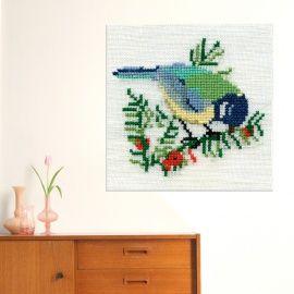 Van een klein retro borduurwerkje naar een grote vogel voor aan de muur: een koolmeesje op een tak met rode besjes. Het originele borduursel is flink uitvergroot, dat geeft een heel bijzonder effect.