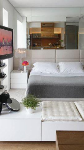 O espelho (Ilha dos Cristais) sobre a cama, com cabeceira estofada com linho, ajuda o espaço a parecer maior. Colcha e lençóis da Trousseau, tapete da Século.