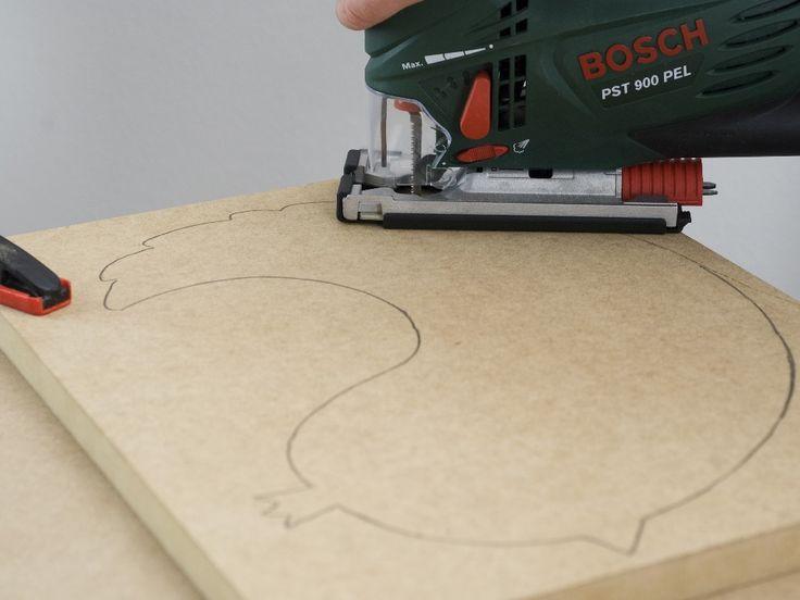 Pasul 7: Îmbinarea plăcii de contur/plăcii frontale cu taburetul Executaţi cu maşina de găurit şi burghiul pentru lemn de 4 mm câte două găuri pătrunse în latura îngustă a picioarelor şi adânciţi-le dinspre spate. Fixaţi placa în menghine, la înălţimea dorită sau conform specificaţiilor din schiţa noastră. În final, înşurubaţi placa, din partea din spate, prin picioarele scaunului, cu maşina de înşurubat cu acumulator şi şuruburi cu cap înecat de 4 x 90 mm.