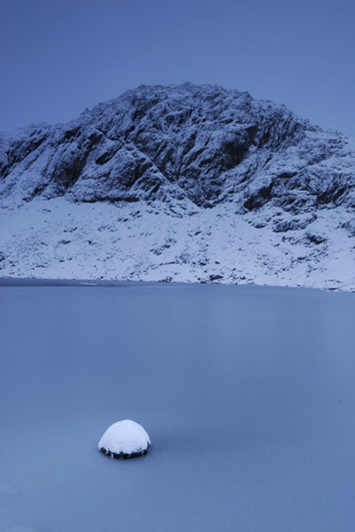 The summit of Pavey Ark, the end of a rewarding Wainwright walk, as viewed from a frozen Stickle Tarn