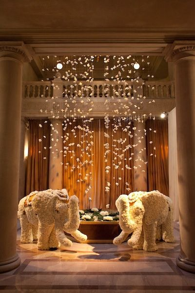 Love this modern indian wedding idea - elephants at the venue entrance (in white flowers) and hanging flowers from the ceiling. Brings such elegance and romance to the venue - it's modern yet still Indian. Great idea for fusion wedding decor too!