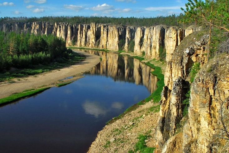 Уникальные каменные образования начали формироваться на территории России 540-560 миллионов лет тому назад. В спокойных водах реки Лена величественно отражаются эти красные песчаные столбы.