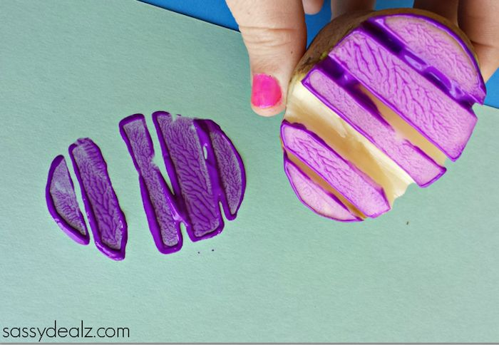 potato stamp covered in paint, held by hand with pink nail polish, easter crafts for preschoolers, sheet of pale green card, with purple easter egg-shaped print