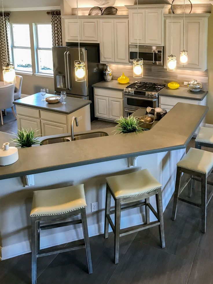 Off-white kitchen cabinets with gray countertop and yellow accents make this kitchen an ...