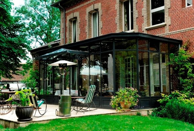 Photo : véranda de style contemporain avec toiture 3 pentes et 2 pans coupés