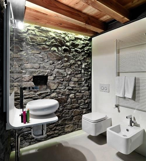 #reforma #baño moderno en vivienda rural, sanitarios flotantes, pared de piedra, techos de madera y suelo resina epoxi.
