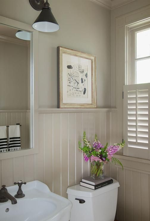 Cottage powder room features upper walls painted taupe and lower walls clad in taupe beadboard ...