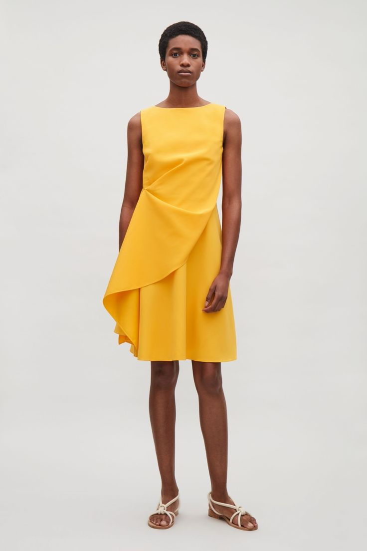 A heavy lined woven dress with an asymmetric gathered side creates a waterfall panel that drapes diagonally at the front. A sleeveless round neck, this dress has a concealed zip fastening, flared hem and topstitch finishes.