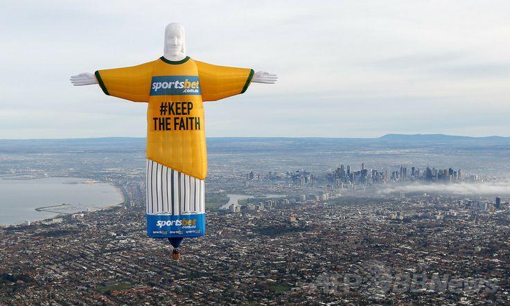 豪メルボルン(Melbourne)上空に出現した、サッカーW杯ブラジル大会(2014 World Cup)のオーストラリア代表ユニフォーム姿の「コルコバードのキリスト像(Christ the Redeemer)」を模した気球(2014年6月10日撮影、提供写真)。(c)AFP/Sportsbet.com.au/David CALLOW ▼11Jun2014AFP|キリスト像の巨大気球出現、代表ユニ着て応援 豪メルボルン http://www.afpbb.com/articles/-/3017343