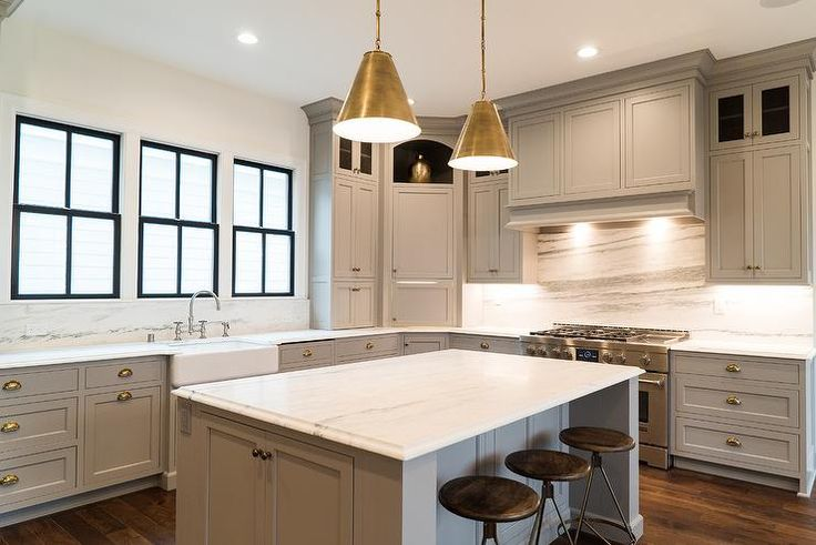Stunning gray and gold kitchen features three black framed windows positioned above an apron sink paired with a polished nickel deck mount gooseneck faucet mounted to a honed Arabescato Danby Marble countertop accenting gray shaker cabinets painted in Benjamin Moore Cape May Cobblestone and finished with brass cup pulls.