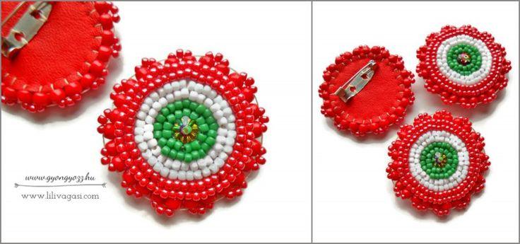 Gyöngyhímzéssel készült kokárda japán toho gyöngyökből, közepén csillogó crystal vitrail swarovski virág felhasználásával, hátulja tűzpiros bőr. Egy kokárda is lehet ékszer! Mérete: kb. 3,8 cm - 2600,-ft/db.