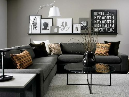 Composição de quadros em preto e branco com tamanhos variados apoiados em prateleira única acima do sofá numa decoração com paleta de cores escura e sóbria