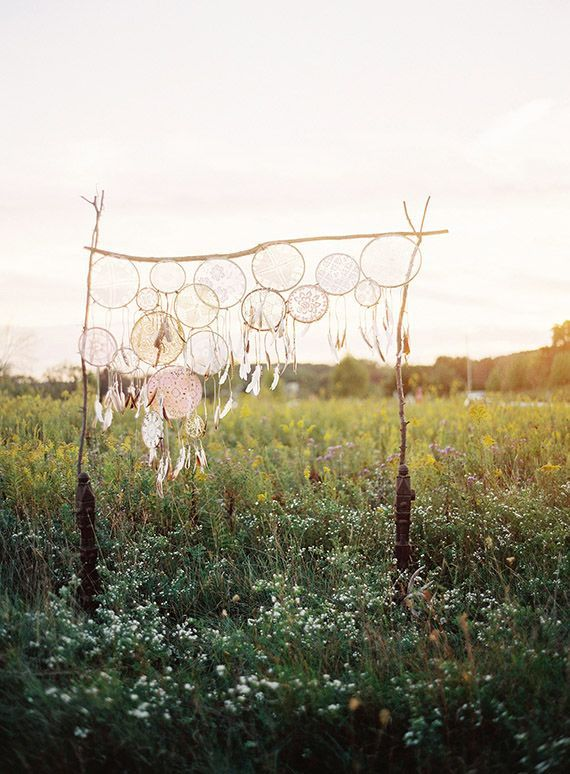 Une arche constituée d'attrape-rêve pour un mariage bohémien laïque en plein air.