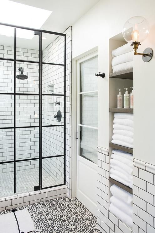 White and black bathroom boasts an alcove filled with shelves holding towels alongside a white and black floor in Cement Tile Shop Bordeaux Tiles.                                                                                                                                                                                 More