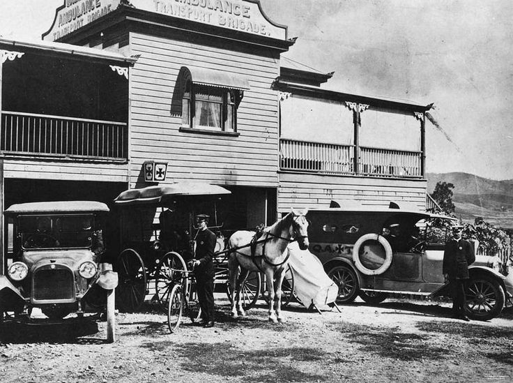 Ambulance officer standing beside a horse drawn vehicle outside the Ambulance Transport Brigade building at Mount Morgan, ca 1921. Two other motor vehicles are parked nearby. The Queensland Ambulance Transport Brigade insignia is on the wall above the entry doors. The car in the left is a 1915 Dodge. Only in 1914/15 did the Dodge have the mudguards coming back into the sides of the radiator. After 1915 they went to the front of the springs.