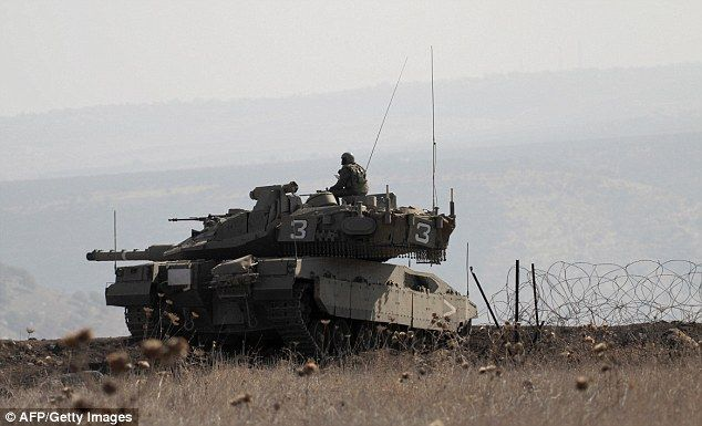 Israeli soldiers on a tank monitor the Golan Heights today after four ISIS gunmen attacked Israeli forces in the area before being killed by an air strike