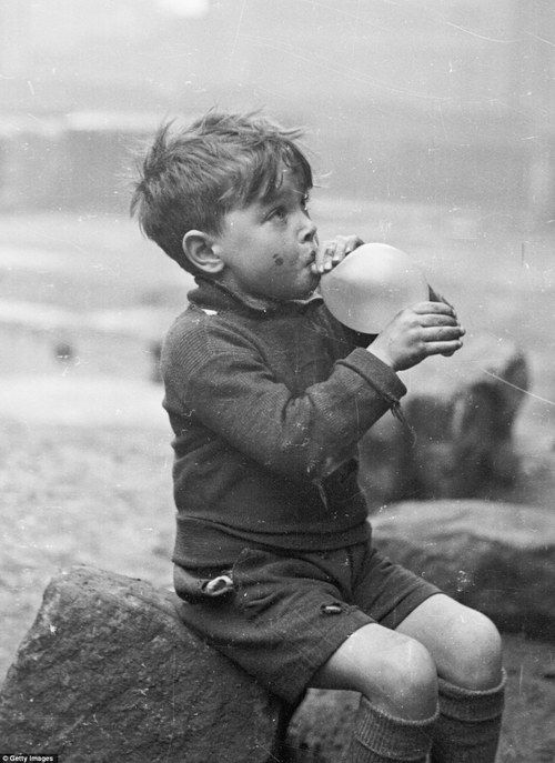 A young boy blowing up a balloon in the Gorbals, Glasgow  in 1948 - photo by Bert Hardy