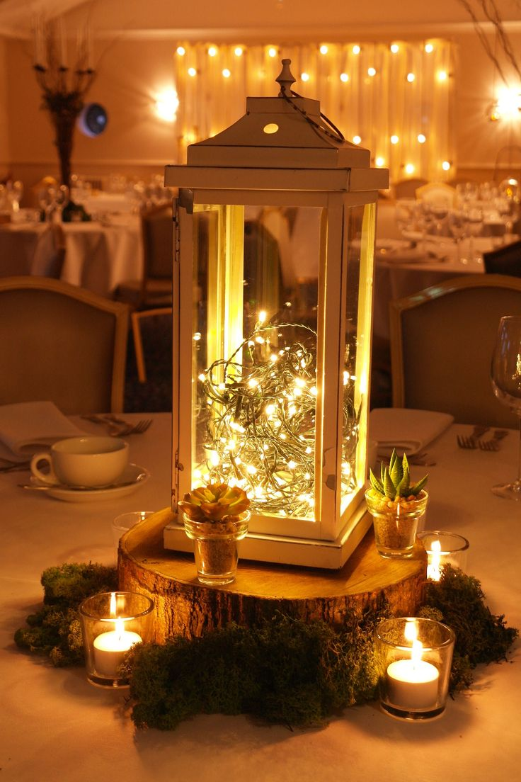 Wooden slice table centre with moss, succulents, votives and a vintage-style lantern with pealights by www.stressfreehire.com #venuetransformers