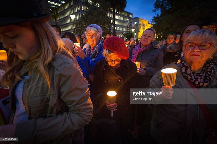 A woman takes a minutes silence in rememberence of Aylan Kurdi on September 7, 2015 in Melbourne, Australia. Thousands of people around Australia gathered to remember Aylan Kurdi, the young Syrian refugee who died last week and to protest the Australian Government's current refugee policy.