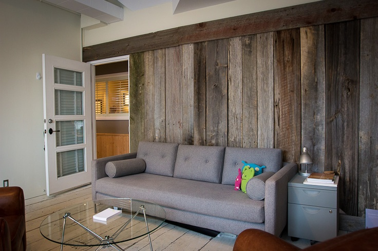 Barn-door wood panelling, midcentury-modern sofas and Ugly dolls are a match made in interior design heaven.