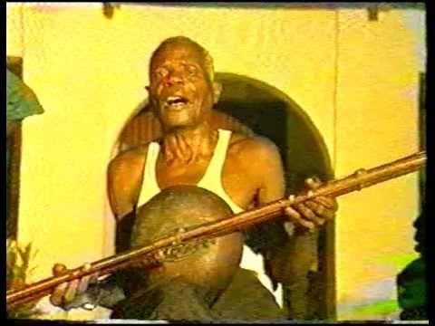 """Le regretté Marcel MBOUMA, grand chanteur de la danse EKONGO, psalmodiant une mélodie """"bellonique"""" au rythme d'un instrument à cordes appelé Lengombi."""