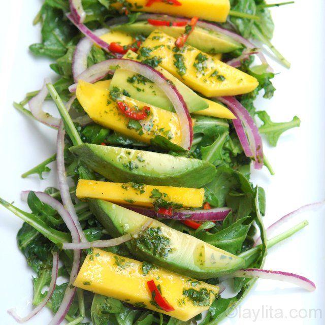 Receta para preparar una refrescante y colorida ensalada de mango, aguacate, rúcula, y cebolla con aderezo o vinagreta de naranja.