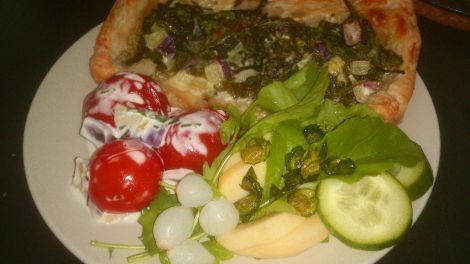 bladerdeeg-pizza met spinazie, perzikkruid en geitenkaas, gepofte tomaatjes in geitenkaas-roomsaus en een salade van verse rucola met appel, komkommer, uitjes en een krokantje van gebakken herderstasje/witte krodde zaadjes.