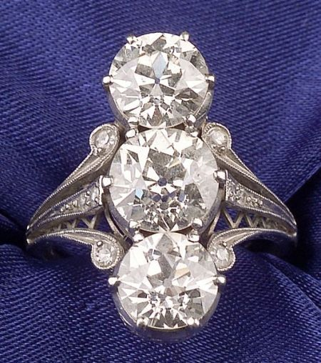 Art Deco Platinum and Diamond Three-stone Ring, Gattle, prong-set with three old European-cut diamonds weighing approx. 1.29, 1.87, and 1.31 cts., the scrolling shoulders bead-set with eight old single-cut diamond melee, engraved highlights, open gallery with millegrain accents, approx. total diamond wt. 4.55 cts.