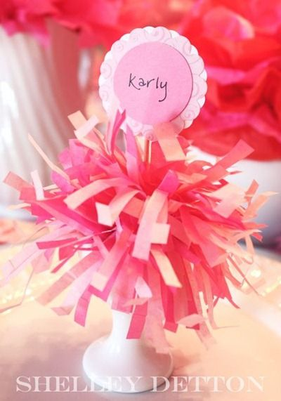 Pom Pom Name Card. I would change the actual card, as it seems less kapow than a card attached to a pink pom pom should be! :) You know I love the pink, but my daughters have done cheerleader birthday parties for little girls & so one could change the color of the pom pom to fit the colors of the school! I think for a cheerleader party one could add the name card in the shape of a pennant! COOL!