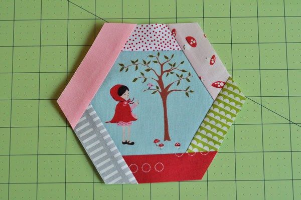 Isn't she cute?For this block, you will need:Basic sewing suppliesRotary cutter and matHexagon ruler or template. I have created a 4″ and 5″ template for you, click HERE.An assort…