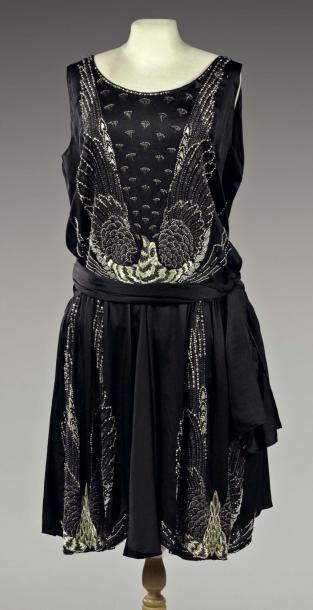 * BEL OISEAU Robe du soir vers 1928 Satin de soie noir, broderies en perles de cristal, perles artificielles, tubes de jais et perles de verre blanc laiteux. Motifs brodés de faisans aux ailes déployées sur le devant - attribuée à Jeanne Lanvin.