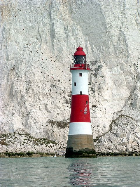 Beachy Head Lighthouse in Sussex England. It was brought into service in 1902 to replace the Belle Toute lighthouse on the cliff top near Eastbourne. The lighthouse will be allowed to return to natural granite because the cost of painting it red and white can no longer be justified.