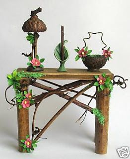 Beautifully Detailed Little TWiG TaBLE, BaSKET, LaMP CaNDLEHoLDER. These take fairy furniture to a whole new level. Inspiration only, but I love seeing what they did with the acorn caps and the tiny decorative flowers ___The Whittaker's Miniatures