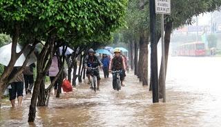 Pekerja bersepeda melintasi banjir di jalan Thamrin, Jakarta, Kamis (17/1). Sepeda menjadi kendaraan alternatif saat jalan tidak bisa dilalui kendaraan bermotor