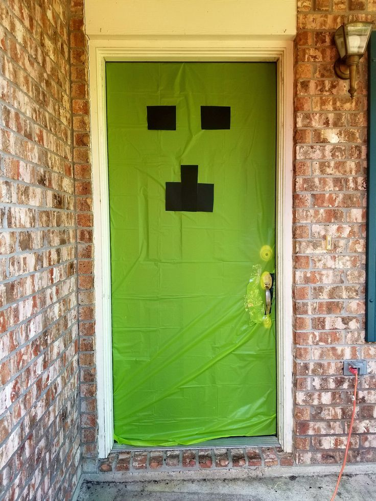 We were going with a Minecraft party theme this year! The only problem is it is hard to find Minecraft Party supplies so you have to be very creative if you want a Minecraft party theme. So I heard Pinteret calling my name. I was so inspired so I decided to share our Minecraft Party ideas with you. We had alot of DIY projects for this fun party and it was awesome. For the door we used a lime green tablecloth and cut out the creeper face with black construction paper.