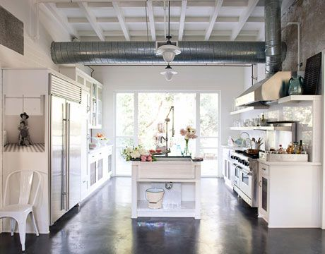 In the kitchen, industrial elements like exposed air ducts, polished concrete floors, and stainless-steel appliances are warmed up with open shelving and vintage accessories and hardware. Island sink by Michael S. Smith for Kallista. Thassos white marble counters and backsplash from Walker Zanger. Viking range; vintage French pendants from Obsolete.