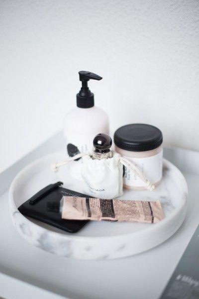 Ved å samle krukker og produkter på f.eks et marmorfat så skaper man et mer ryddig uttrykk på badet