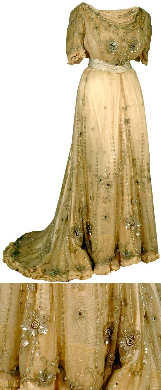 """Dress, 1907. Waistband has woven mark reading, """"Denova, 32 Avenue de l'Opera, Paris."""" An example of the Pouter Pigeon style, this is made of off-white cotton net heavily trimmed w/blue sequins, beads, & satin. Skirt is tulip-shaped (its design resembles an upside-down tulip by curving outward at the bottom). Bodice & skirt have large, pale blue flowers formed of petal-shaped sequins & opalescent seed beads, with centers of small brown sequins & silk chenille thread. Sashed waist."""