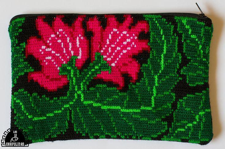 Estuche hecho a mano con bordado tradicional tzeltal. El diseño tiene dos flores medianas en la esquina izquierda color rosa mexicano y dos hojas grandes de un verde intenso. Fue bordado con punto cruz muy apretado y firme. La parte posterior es de manta negra, tiene un cierre en la parte superior y forro. Productoras: Cooperativa textil Skinal Nichimetik Origen: Pueblo Nuevo Sitalá, Los Altos de Chiapas, México. Técnica: Punto Cruz Medidas: Ch: 9 x 14 cm Med: 10,5 x 17 cm Gr: 12 x 20 cm