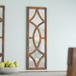 Evoke chic modern countryside allure and decadent Art Deco flair in any space of your home with this charming wall mirror. The geometric openwork details set on top of the rectangular mirror gives this decor its modern style, while the warm brown finish and visible grain details round out the look in traditional style. A classic combination with versatile appeal, this mirror offers stately style for every space. Try hanging this elegant mirror against a wall in your master suite to liven up…