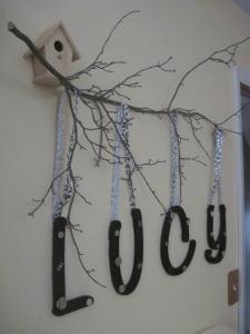 DIY tree branch nursery decor, but it could also be really cool with photos hung from ribbons instead of the letters.