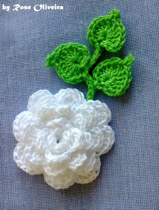 white crochet rose with perfect rose shaped leaves.