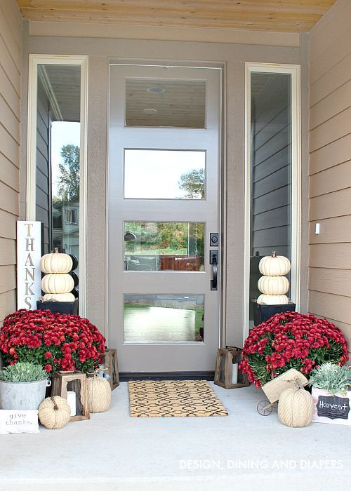 Front door with 4 window panes.  Neutral Fall Porch with Mums