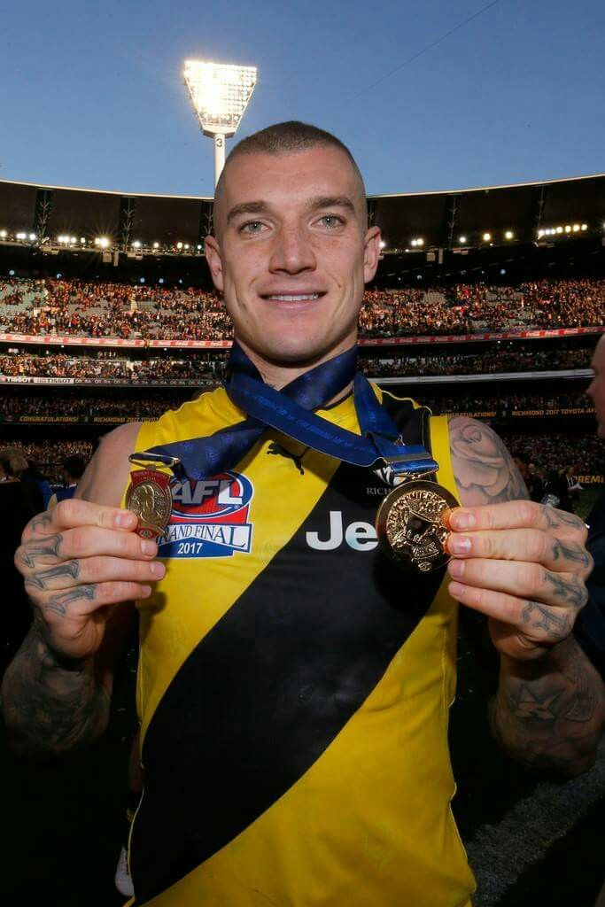 Dustin Martin with premiership medallion and Norm Smith Medal