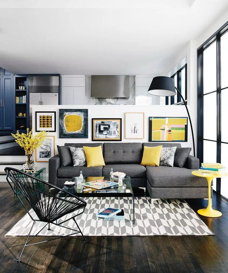 Idea soggiorno moderno contemporaneo con vari quadri e tocchi di colore giallo. Pavimenti parquet in legno. Open space con salotto, cucina e sala da pranzo