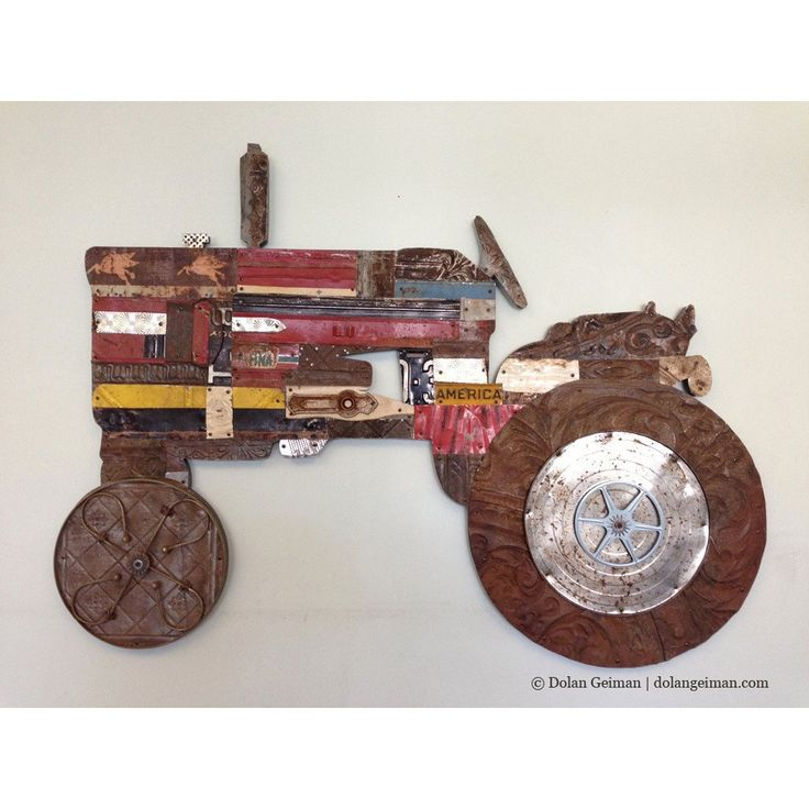 Vintage tractor eco artwork composed from salvaged metal and found objects, featuring rustic golden hues and copper tones. Industrial farmhouse wall decor.